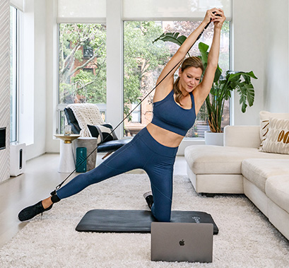 Woman kneels on mat and extends one leg out while following along with a class on her computer