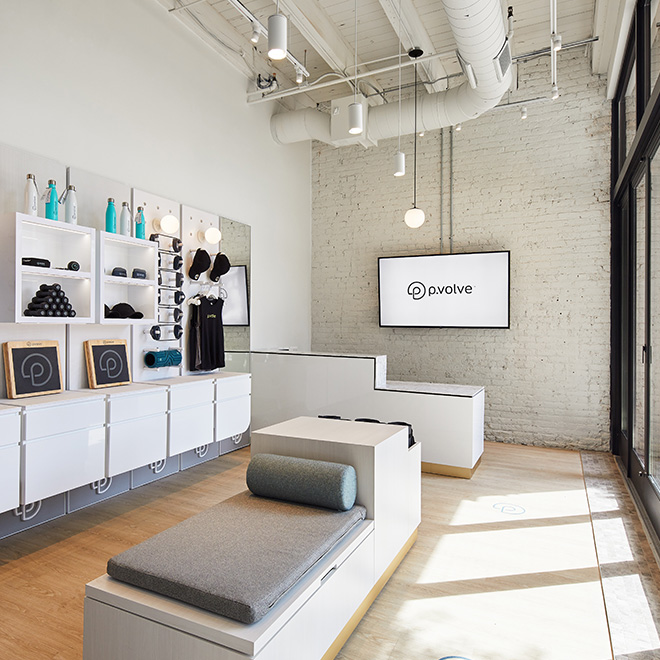 P.volve's industrial inspired lobby features white shelving, branded merchandise and P.volve equipment