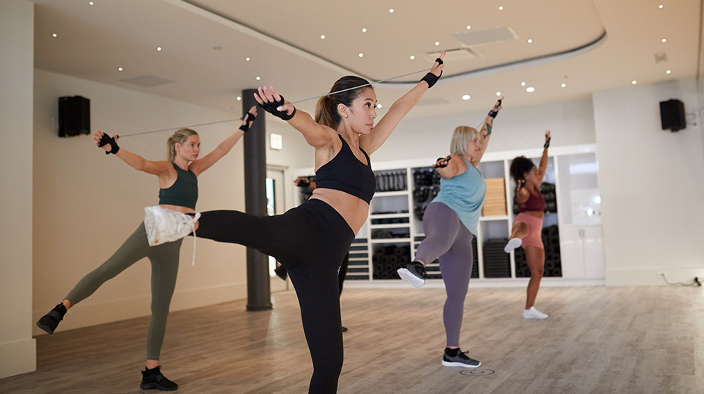 Group of diverse women perform exercise using p.bands